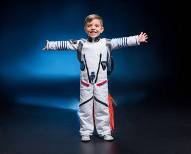 Happy little boy in astronaut costume laughing at camera stock vector