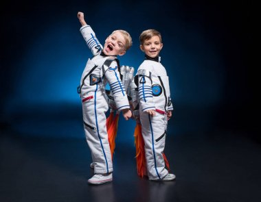 Two cute little boys in space suits standing back to back looking at camera stock vector