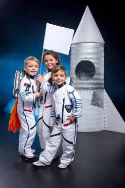 Two little boys and girl in space suits holding flag near rocket  and smiling at camera stock vector