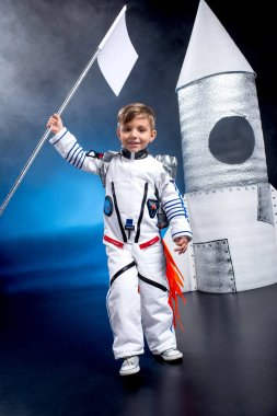 Little boy astronaut in space suit with flag standing near rocket stock vector