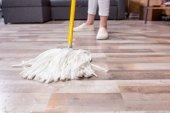 žena čištění podlahu mopem