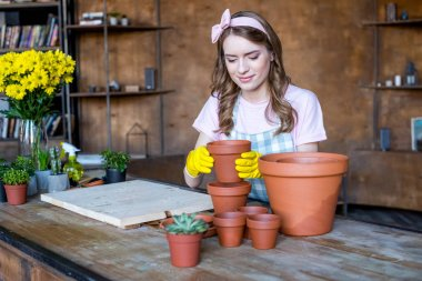 Smiling beautiful young woman in rubber gloves holding empty flowerpot stock vector