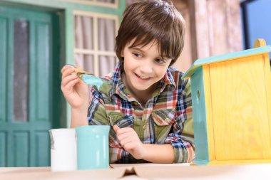 Boy making birdhouse