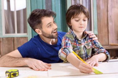 Portrait of father helping concentrated son to take measures of wooden plank in workshop stock vector