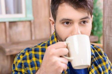 man holding cu of tea