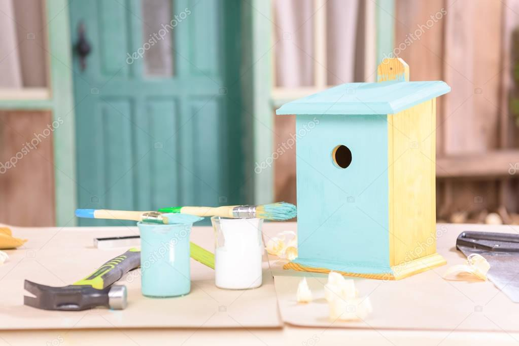 Birdhouse with paints and tools