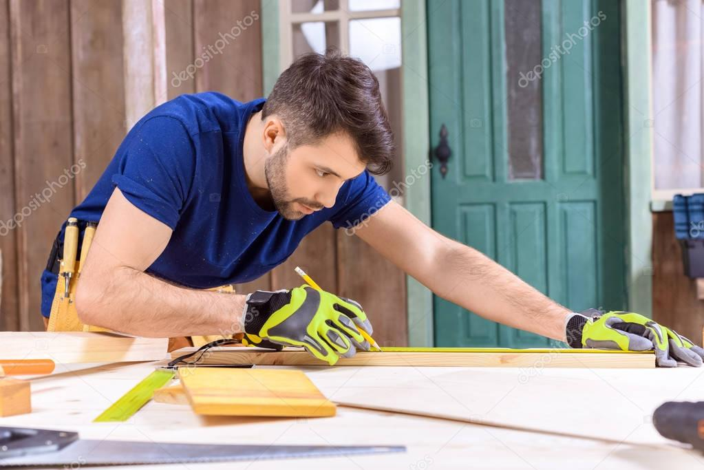 carpenter working with wooden plank