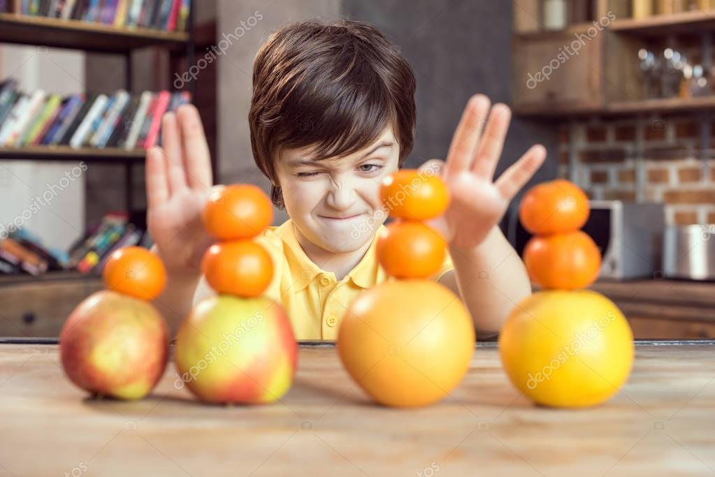 Boy playing with fruits