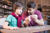Fotografie father and son palying with puzzles