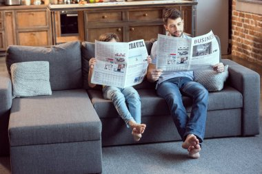 father and son reading newspapers