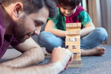 father and son playing jenga