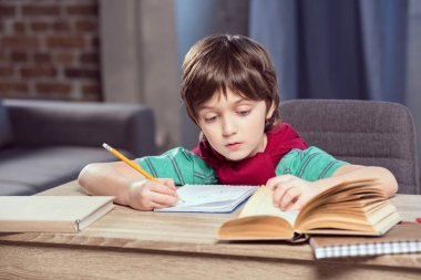 Portrait of concentrated boy sitting at table and doing homework stock vector