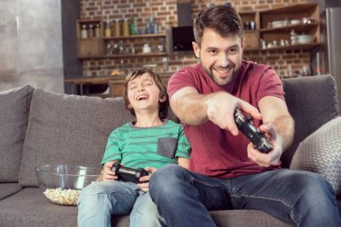 Cheerful father and son playing video game at home stock vector