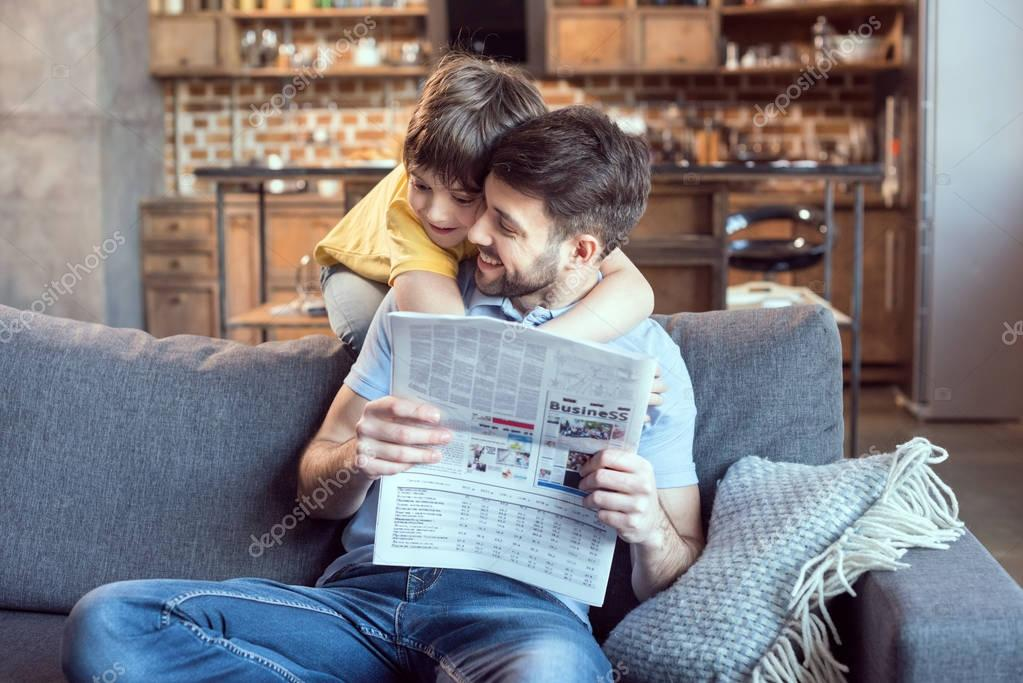 Father and son reading newspaper