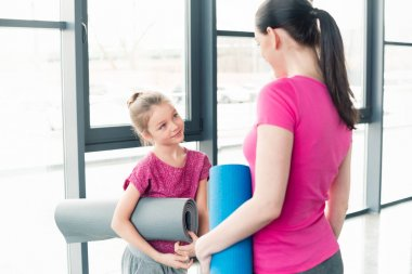 Mother and daughter with yoga mats