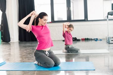 mother and daughter sitting on yoga mats