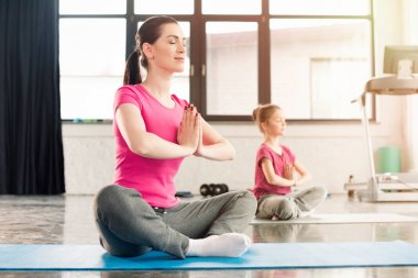 mother and daughter in lotus pose
