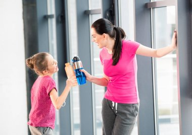 mother and daughter with sport bottles