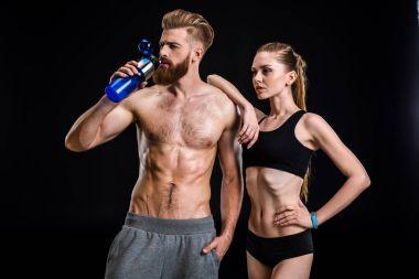 sportsman with sport bottle and sportswoman