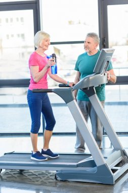 senior couple training on treadmill