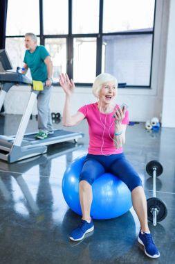 senior sportswoman sitting on fitness ball