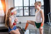 Fotografie Kleine Jungen und Mädchen in Sportbekleidung im Gespräch