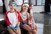 Kinder sitzen auf Reifen im Fitnessstudio