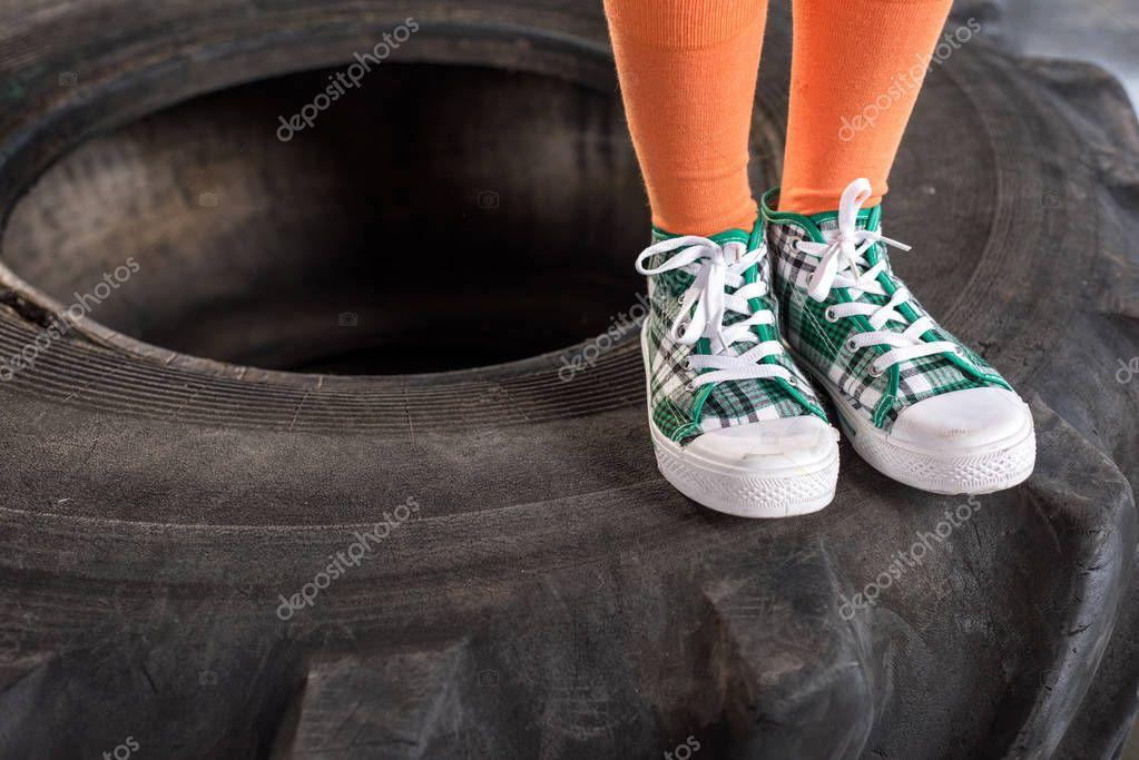 child in sportswear standing on tire