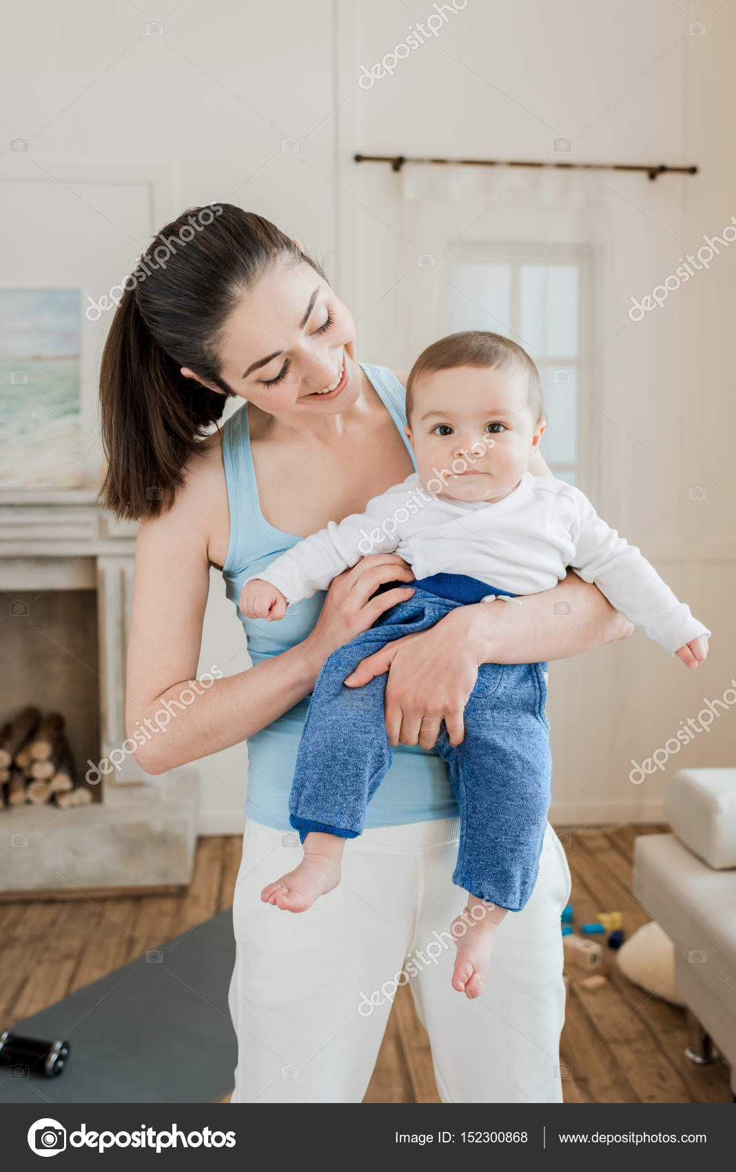 Woman Carrying Baby Child On Arms Stock Photo