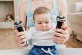 nő és a baba fiú játszik a súlyzó