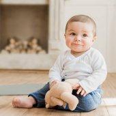 Usměvavý chlapeček sedící medvídek