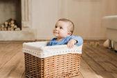Junge sitzt in geflochtener Schachtel