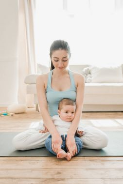 Woman with child sitting in lotus position
