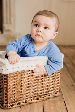 Baby boy sitting in braided box