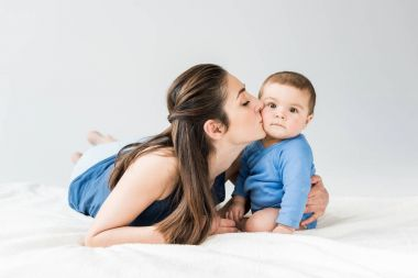 Young mother with child lying on bed