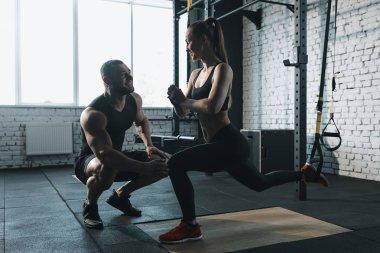 sportswoman squatting with trx