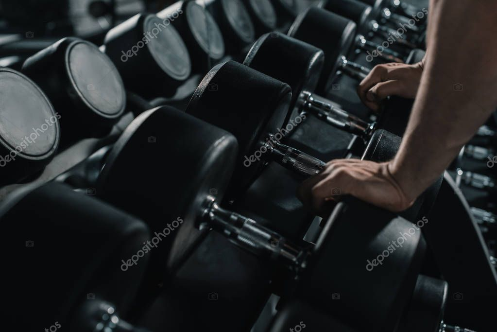 sportsman taking big dumbbell