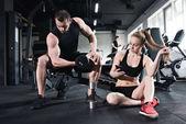 muži trénink, zatímco žena pomocí smartphonu