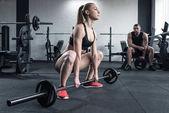 Žena, která dělá silový trénink zároveň muž sedící