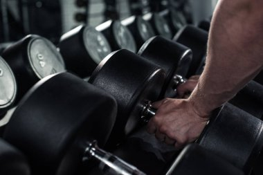 man taking dumbbells at gym