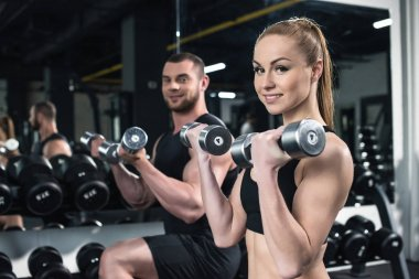 young couple training with dumbbells together