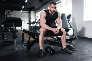 sportsman sitting at gym looking at camera