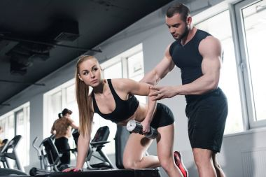 Instructor helping young woman with dumbbell
