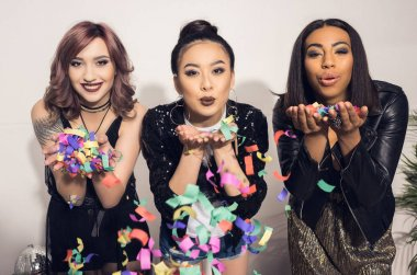 young multiethnic girls blowing confetti