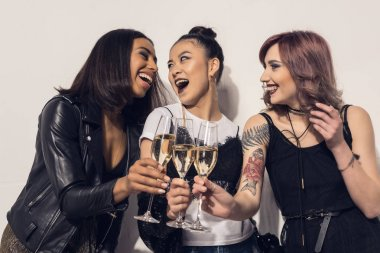 happy multiethnic girls drinking champagne
