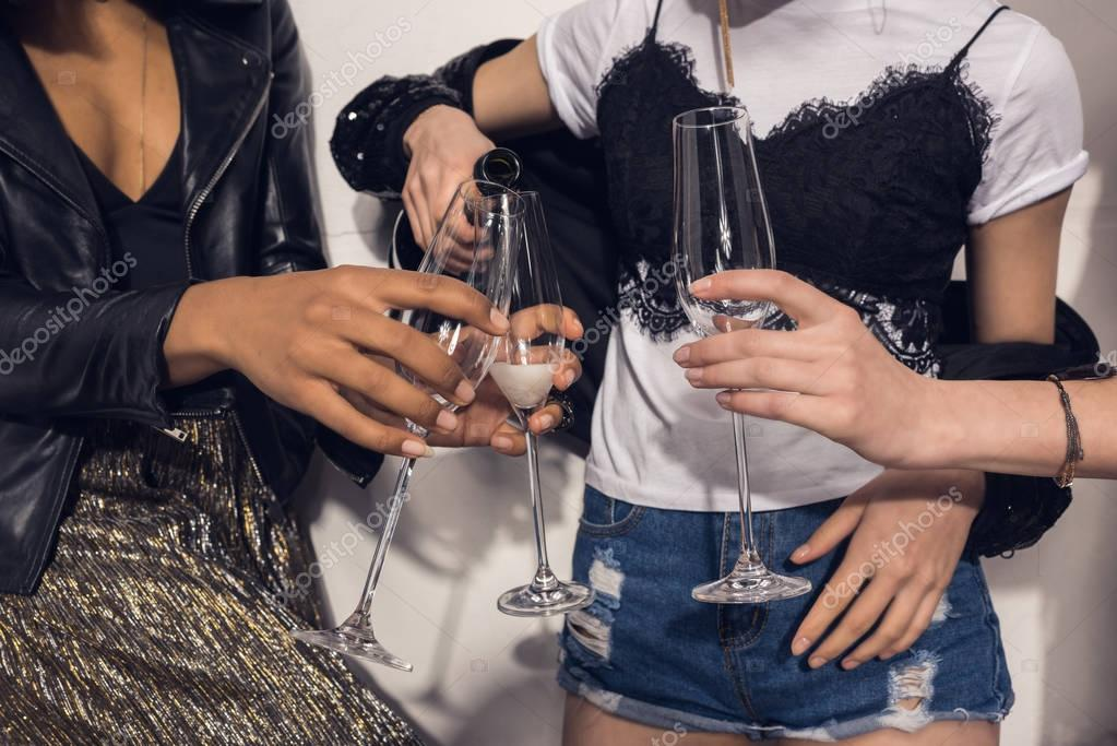 young girls pouring champagne into glasses