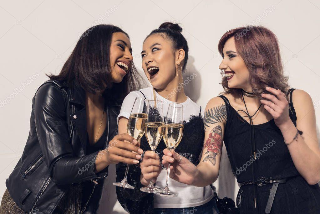 happy multiethnic girls drinking champagne