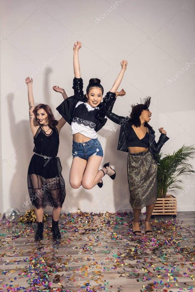 cheerful multiethnic girls jumping at party