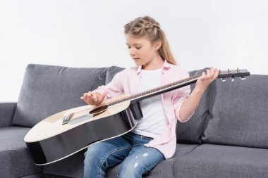 girl practicing to play on guitar