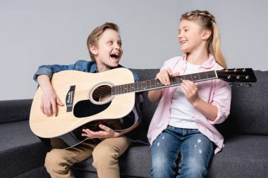 siblings playing on guitar together